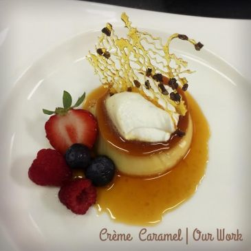 Traditional creme caramel topped with whipped cream, decorative caramel, and fresh berries.